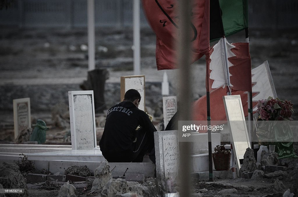 A Bahraini man sits near a grave of a victim of violence as protestors clash with riot police following an anti-government rally to demand political reforms on February 13, 2013 in the village of Sitra, South of the Bahraini capital, Manama. Thousands of Bahraini Shiites took to the streets on the eve of the second anniversary of their crushed uprising, as a national dialogue aimed at ending a political stalemate resumed.