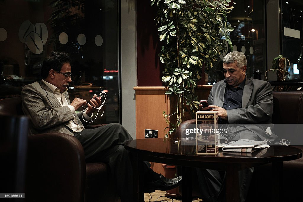 Bahraini men browse twitter on their smartphone in a coffee shop in the capital Manama on January 29, 2013. Twitter's unmatched platform for public opinion is emboldening Gulf Arabs to exchange views on delicate issues in the deeply conservative region, despite strict censorship that controls old media.