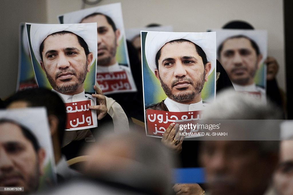 Bahraini men hold placards bearing the portrait of Sheikh Ali Salman, head of the Shiite opposition movement Al-Wefaq, during a protest on May 29, 2016 against his arrest, at Al wefaq headquarter building, in the village of Zinj on the outskirts of the capital Manama. / AFP / MOHAMMED