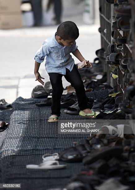 A Bahraini Muslim boy takes off his flipflops as he arrives to perform the Friday prayer during the holy fasting month of Ramadan on July 18 2014 at...