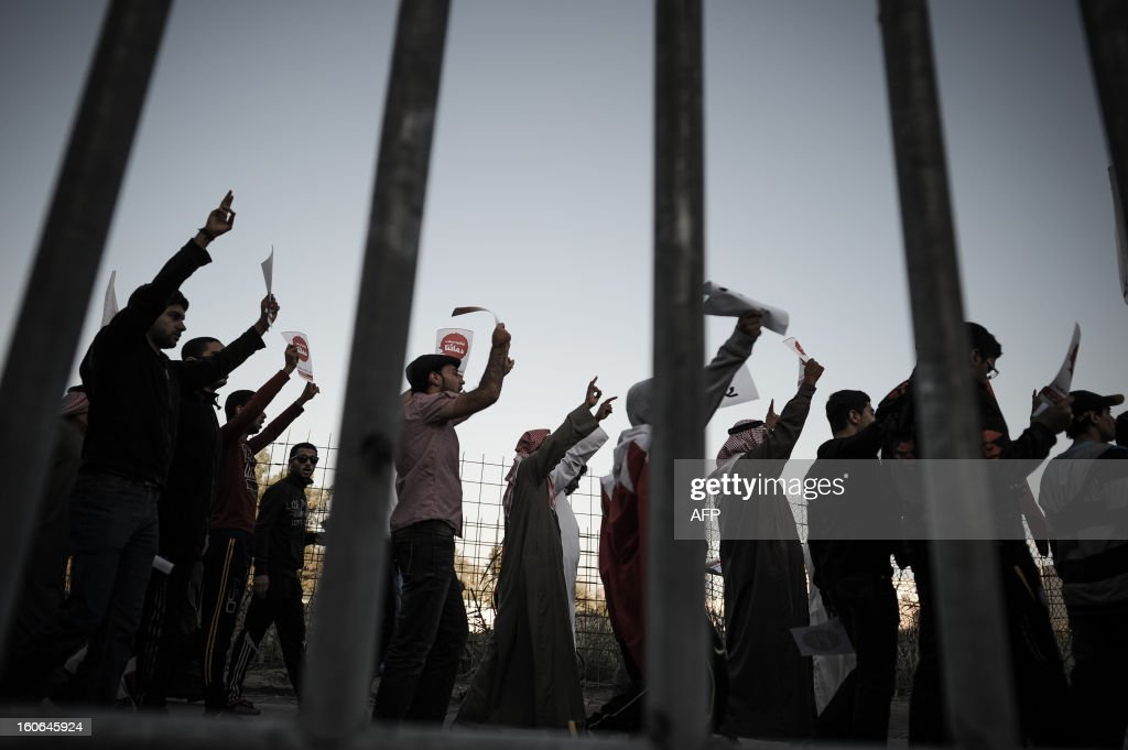 Bahraini people are seen behind a fence as they demonstrate to demand reforms on February 4, 2013 in the city of Muharraq, east of the Bahraini capital Manama. Bahrain's justice ministry announced that national talks aimed to end the kingdom's political stalemate will resume on February 10, 2013 after an earlier round failed to bring the opposition onboard. AFP PHOTO/MOHAMMED AL-SHAIKH