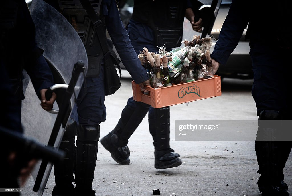 Bahraini police force carry a box full of petrol bombs which was left behind by Muslim Shiite protestors during clashes following an anti-government demonstration on the third day after the funeral of 16-year-old Ali Abbas Radhi in the village of Samahij, near Muharraq City, east of the capital Manama, on November 13, 2012. The Shiite teenager died on November 9, after he was knocked down by a car while being chased by Bahraini police during a crackdown on protesters, the opposition said.