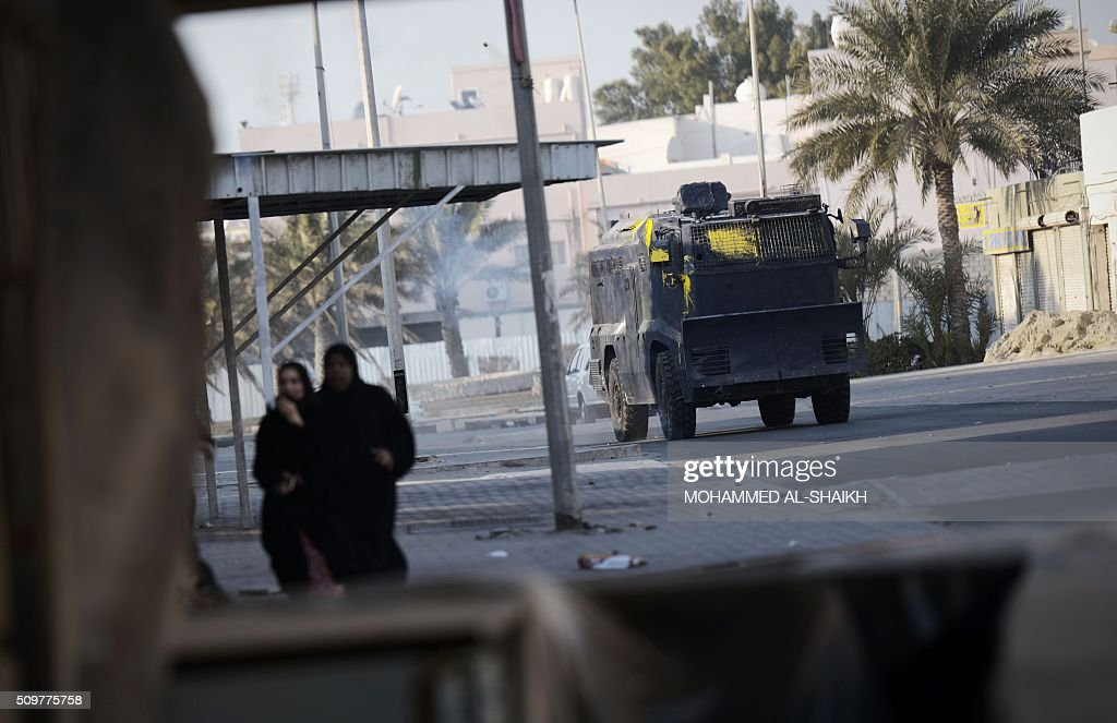 A Bahraini police vehicle drives past women during clashes with protesters following a demonstration to mark the fifth anniversary of the Arab Spring-inspired uprising, on February 12, 2015, in the mainly Shiite village of Sitra, south of Manama. Five years after Sunni-ruled Bahrain crushed a popular uprising by the Shiite majority, the kingdom is locked in a political impasse exacerbated by an economic crisis, analysts say. / AFP / MOHAMMED AL-SHAIKH