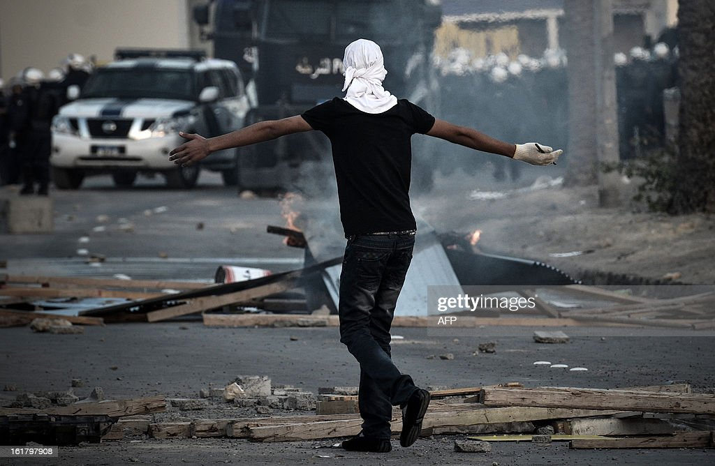 A Bahraini protester gestures towards riot police during clashes following the funeral of a teenager killed in protests marking the second anniversary of a Shiite-led uprising, on February 16, 2013 in the village of Daih, west of Manama. Clashes broke out at the funeral with police using tear gas against mourners, witnesses said.