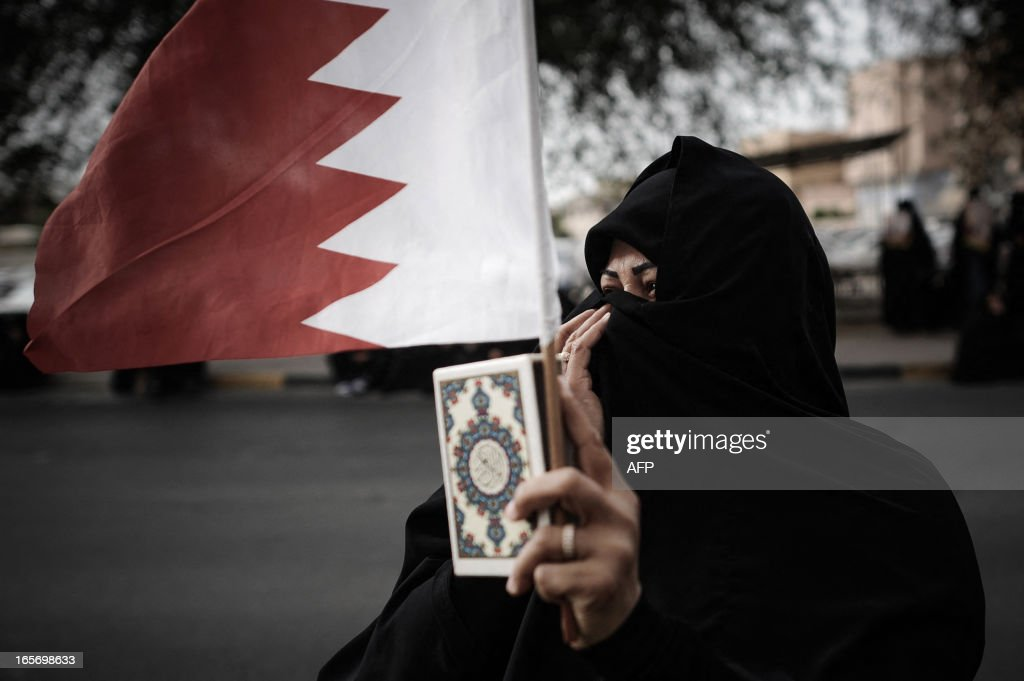 A Bahraini protester holds a Koran, Islam's holy book, along with her national flag as demonstrators call for the reconstruction of Shiite mosques that were demolished by security forces in 2011 during an anti-regime rally in the village of Diraz, west of Manama, on April 5, 2013. The Gulf state has been shaken by unrest since its forces in March 2011 crushed a month of popular Shiite-led protests demanding greater rights and an end to what they said was discrimination by the Sunni royals.