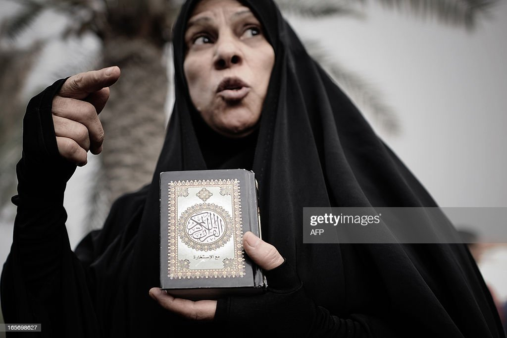 A Bahraini protester holds a Koran, Islam's holy book, as demonstrators call for the reconstruction of Shiite mosques that were demolished by security forces in 2011 during an anti-regime rally in the village of Diraz, west of Manama, on April 5, 2013. The Gulf state has been shaken by unrest since its forces in March 2011 crushed a month of popular Shiite-led protests demanding greater rights and an end to what they said was discrimination by the Sunni royals.