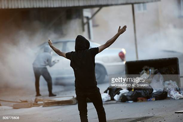 A Bahraini protester shouts slogans during clashes with riot police following a demonstration to mark the fifth anniversary of the Arab...