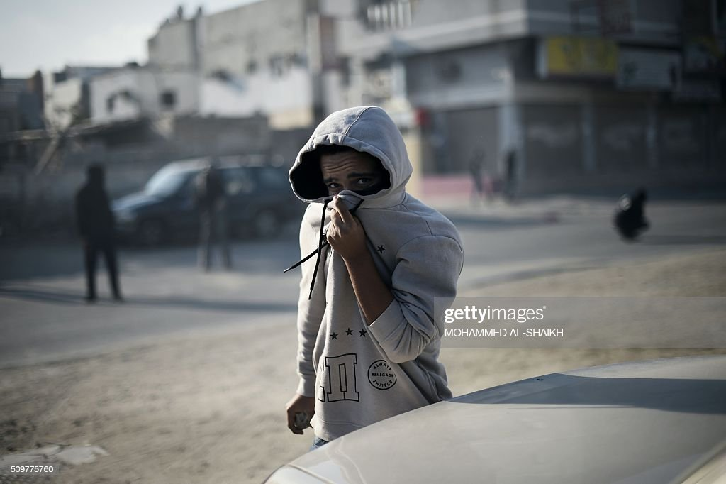 A Bahraini protester takes cover from tear gas during clashes with riot police following a demonstration to mark the fifth anniversary of the Arab Spring-inspired uprising, on February 12, 2015, in the mainly Shiite village of Sitra, south of Manama. Five years after Sunni-ruled Bahrain crushed a popular uprising by the Shiite majority, the kingdom is locked in a political impasse exacerbated by an economic crisis, analysts say. / AFP / MOHAMMED AL-SHAIKH