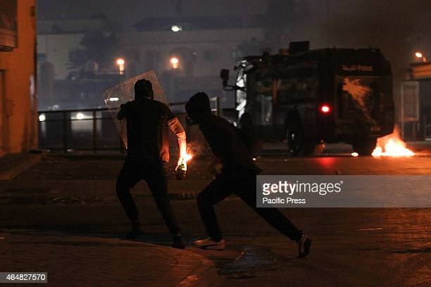 Bahraini protesters hold a localmade armor and Molotov cocktails during clashes with Bahraini regime forces after the issuance of the death sentence...