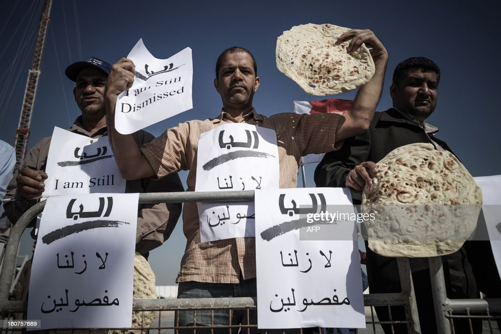 Bahraini protesters hold bread and signs reading in Arabic 'We're still dismissed' during a demonstration, organised by people who were dismissed from their jobs because they attended anti-regime protests, outside the labour ministry in Isa, south of the capital Manama, on February 5, 2013. Many Shiite employees were either dismissed or indefinitely suspended from their jobs in the wake of a brutal crackdown on Shiite-led Arab Spring-inspired protests in March 2011.