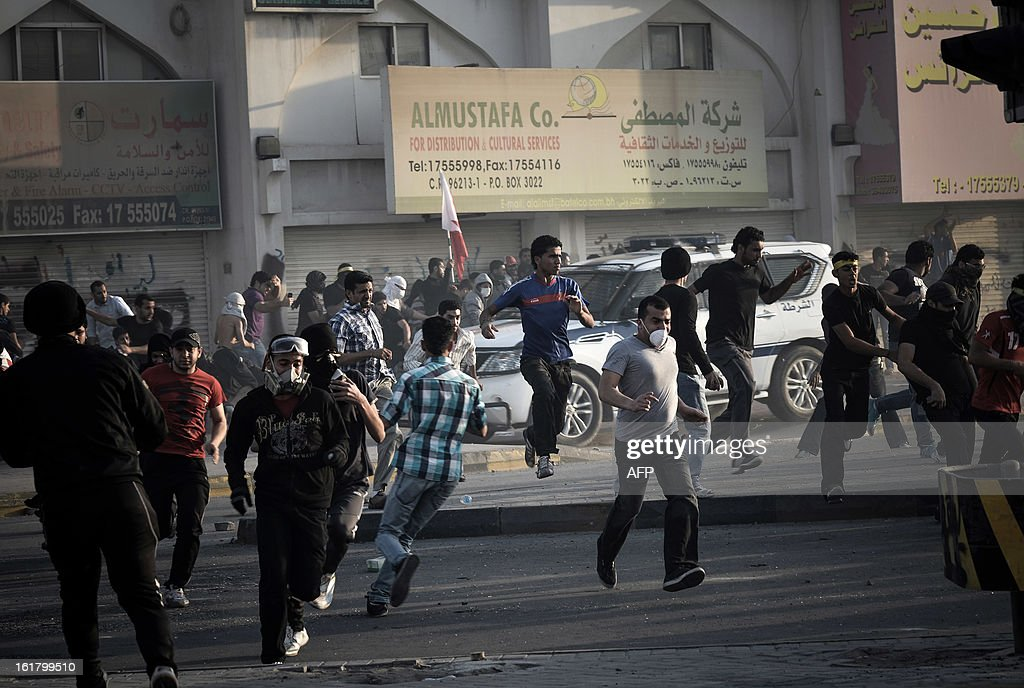 Bahraini protesters rush away after riot police fired tear gas during clashes following the funeral of a teenager killed in protests marking the second anniversary of a Shiite-led uprising, on February 16, 2013 in the village of Daih, west of Manama. Clashes broke out at the funeral with police using tear gas against mourners, witnesses said.
