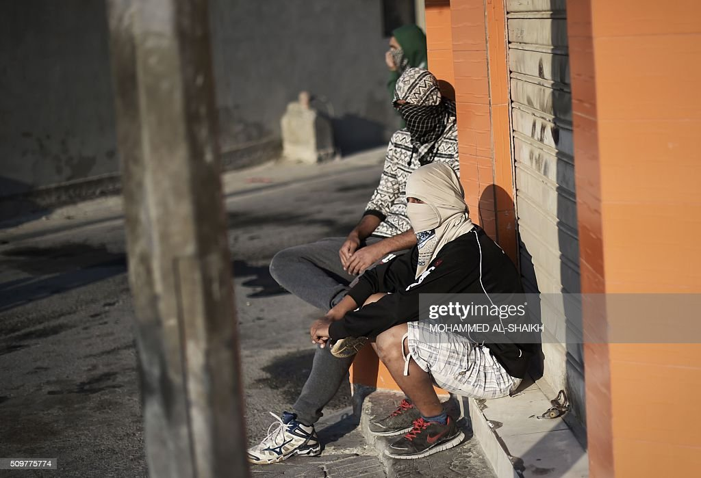 Bahraini protesters sit on the sidewalk during clashes with riot police following a demonstration to mark the fifth anniversary of the Arab Spring-inspired uprising, on February 12, 2015, in the mainly Shiite village of Sitra, south of Manama. Five years after Sunni-ruled Bahrain crushed a popular uprising by the Shiite majority, the kingdom is locked in a political impasse exacerbated by an economic crisis, analysts say. / AFP / MOHAMMED AL-SHAIKH