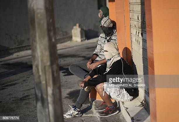 Bahraini protesters sit on the sidewalk during clashes with riot police following a demonstration to mark the fifth anniversary of the Arab...