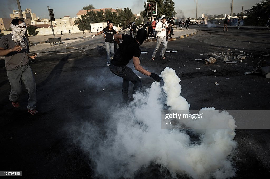 Bahraini protesters throw back tear gas canisters fired by riot police during clashes following the funeral of a teenager killed in protests marking the second anniversary of a Shiite-led uprising, on February 16, 2013 in the village of Daih, west of Manama. Clashes broke out at the funeral with police using tear gas against mourners, witnesses said.