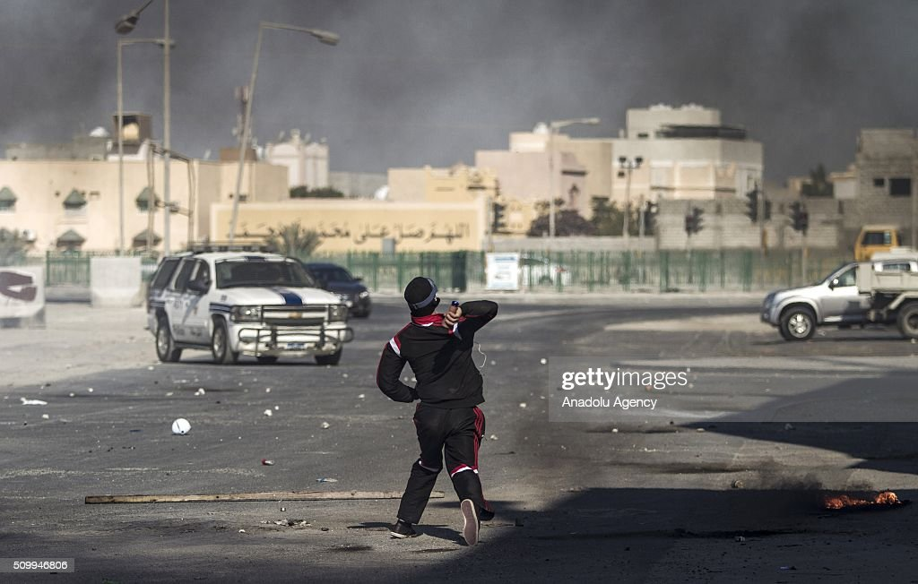 Bahraini protesters throw back teargas canisters toward the security forces during clashes with security forces following a demonstration to mark 5th Bahrain uprising anniversary in Manama, Bahrain on February 13, 2016.