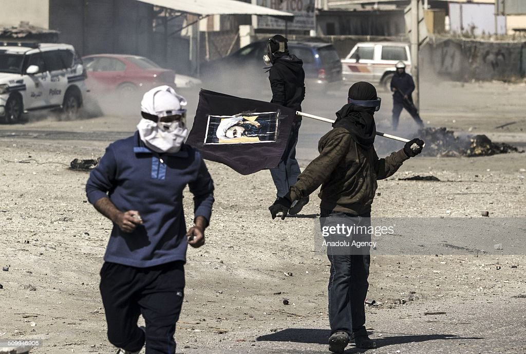 Bahraini protesters throw stones toward the security forces during clashes with security forces following a demonstration to mark 5th Bahrain uprising anniversary in Manama, Bahrain on February 13, 2016.