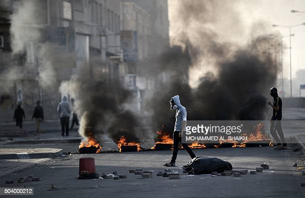 Bahraini protesters walk past burning tyres during clashes with riot police in the village of Sitra south of the capital Manama on January 8...