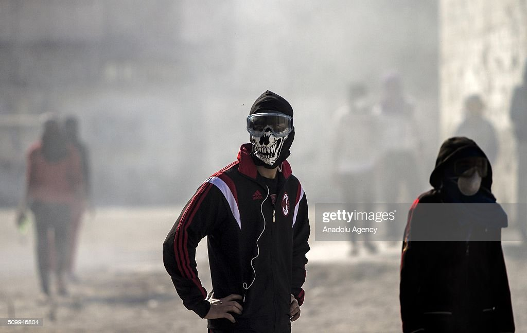 Bahraini protesters wearing masks, are seen during clashes with security forces following a demonstration to mark 5th Bahrain uprising anniversary in Manama, Bahrain on February 13, 2016.