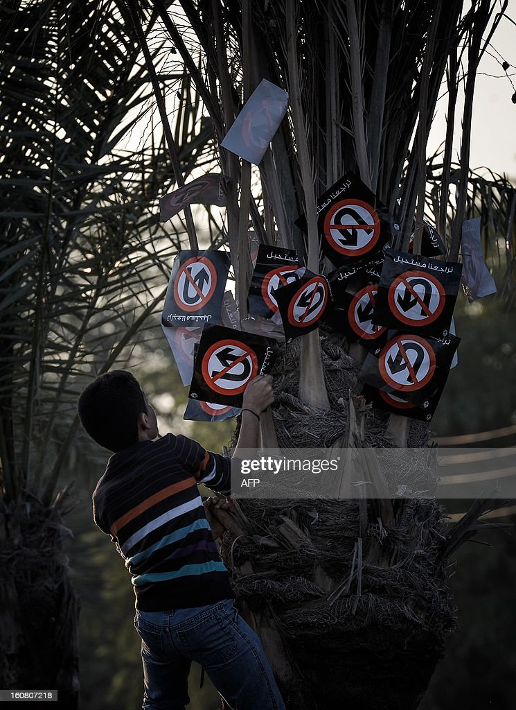 A Bahraini protestor fixes placards reading in Arabic 'our retreat is impossible' on a palm tree during an anti-government rally to demand reforms on February 6, 2013 in the village of Diraz, west of the Bahraini capital Manama.