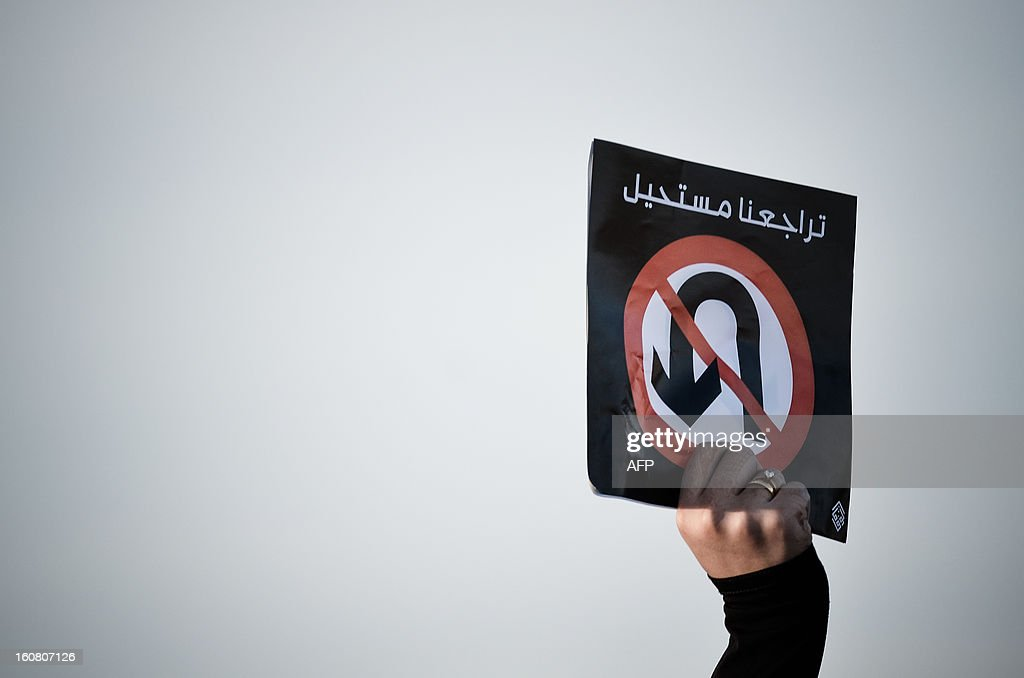 A Bahraini protestor holds a placard reading in Arabic 'our retreat is impossible' during an anti-government rally to demand reforms on February 6, 2013 in the village of Diraz, west of the Bahraini capital Manama.