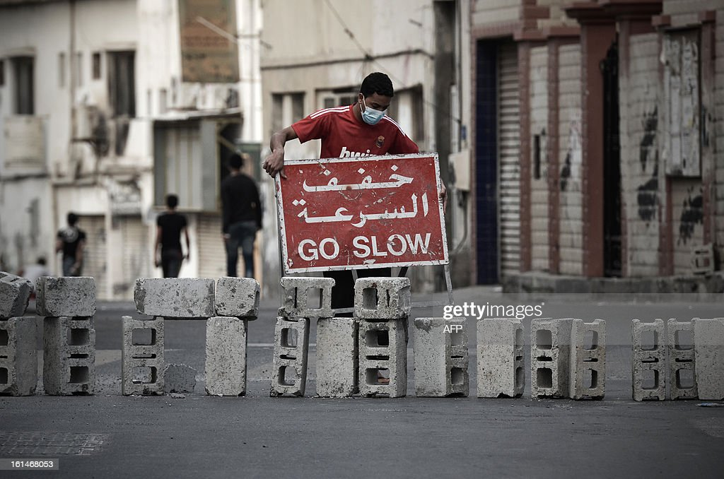 A Bahraini protestor places a traffic sign as they block the road during clashes with police following an anti-government rally against the national dialogue talks on February 11, 2013, in the village of Sanabis, west of the Bahraini capital Manama. Bahrain's key political players launched a new round of talks to try to resolve the kingdom's two-year crisis, after opposition groups made a last-minute decision to join a national dialogue.