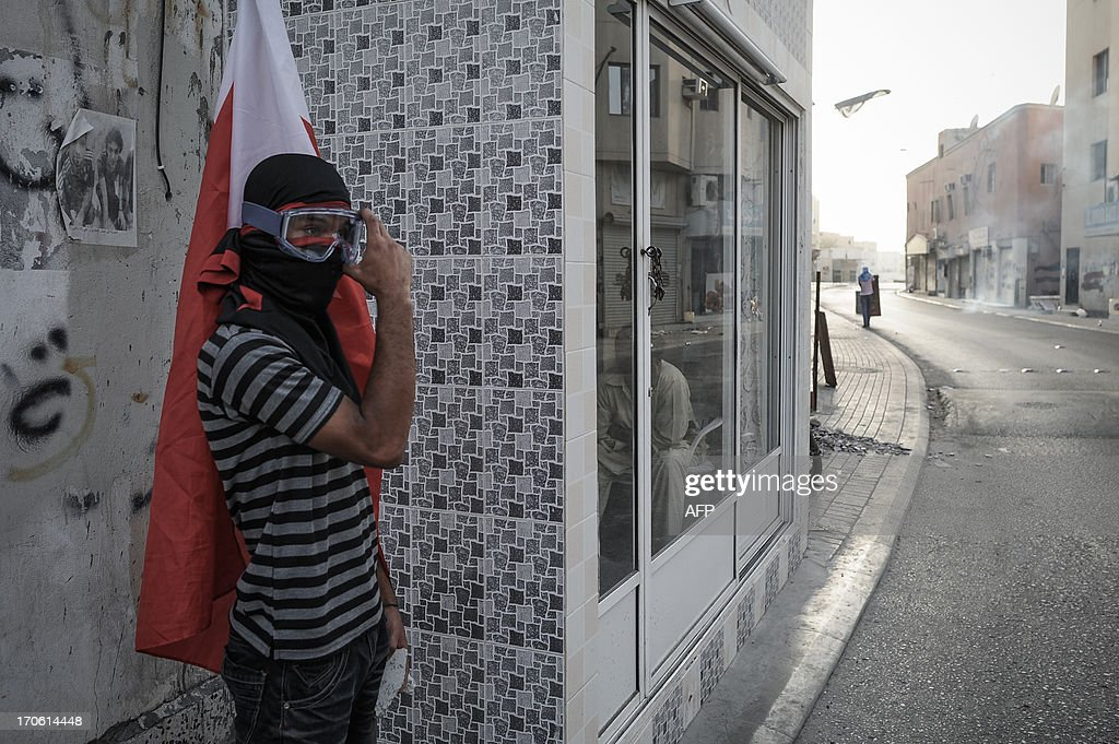 A Bahraini protestor protects himself from tear gas fired by riot police during clashes following a protest to demand more rights and against the ruling regime in the village of Bilad al-Qadeem, in a suburb of Manama, on June 15, 2013. Weekly protests, that began in 2011, are held by Bahraini Shiite Muslims demanding more rights from the ruling Sunni Muslim dynasty.