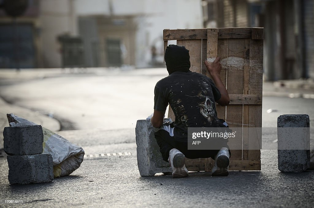 Bahraini protestor protects himself with a wood barrier during with riot police following a protest to demand more rights and against the ruling regime in the village of Bilad al-Qadeem, in a suburb of Manama, on June 15, 2013. Weekly protests, that began in 2011, are held by Bahraini Shiite Muslims demanding more rights from the ruling Sunni Muslim dynasty.
