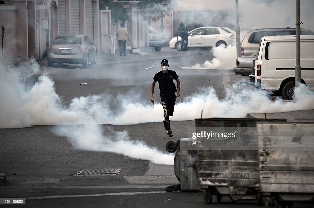A Bahraini protestor runs for cover from rubber bullets and tear gas fired by plainclothes police during clashes following an anti-government rally against the national dialogue talks on February 11, 2013, in the village of Sanabis, west of the Bahraini capital Manama. Bahrain's key political players launched a new round of talks to try to resolve the kingdom's two-year crisis, after opposition groups made a last-minute decision to join a national dialogue.