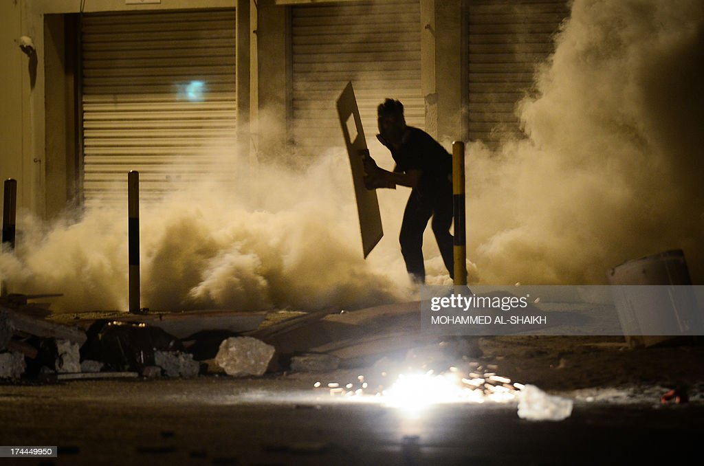 A Bahraini protestor runs for cover from tear gas and birdshot fired by riot police during clashes following a protest against the ruling regime in the village of Diraz, west of Manama, late on July 25, 2013. Bahrain has been shaken by protests by the Shiite majority against the regime of the Sunni Al-Khalifa dynasty since February 2011. AFP PHOTO/MOHAMMED AL-SHAIKH