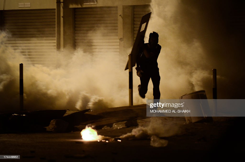 A Bahraini protestor runs for cover from tear gas and birdshot fired by riot police during clashes following a protest against the ruling regime in the village of Diraz, west of Manama, late on July 25, 2013. Bahrain has been shaken by protests by the Shiite majority against the regime of the Sunni Al-Khalifa dynasty since February 2011.