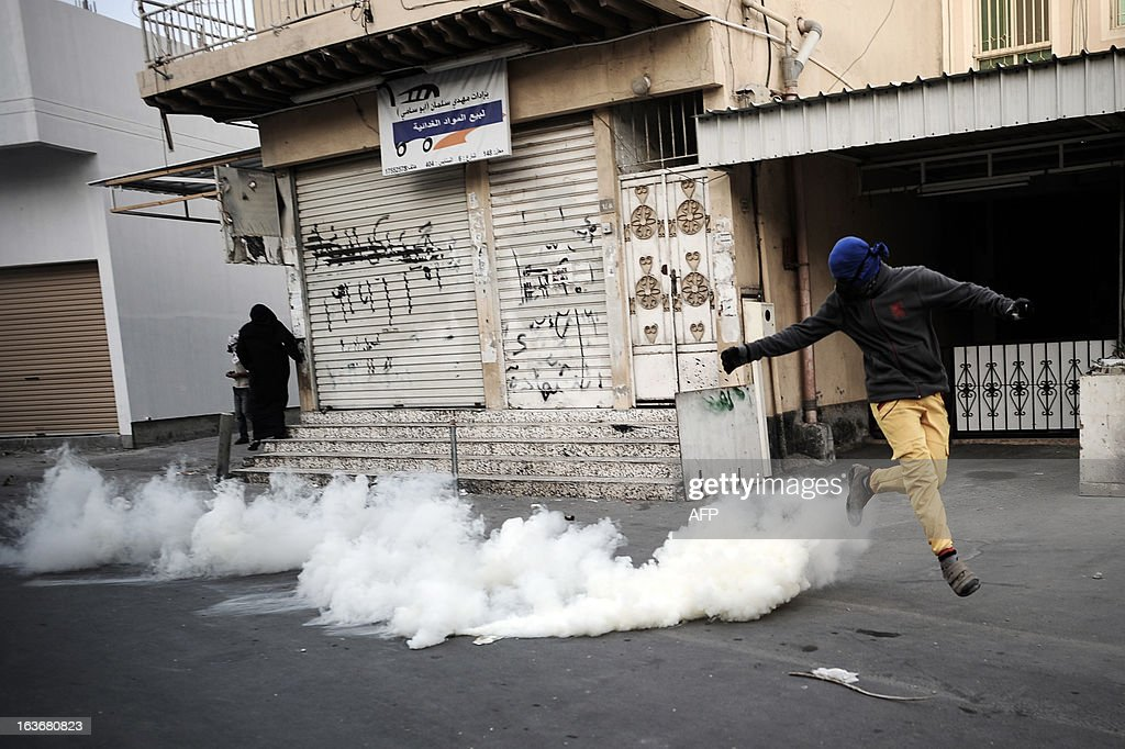A Bahraini protestor runs for cover from tear gas fired by Bahraini riot police during clashes following an anti-regime demonstration in the village of Sanabis, West of Manama, on March 14, 2013. Bahraini police clashed with youths protesting against the deployment into a third year of a Gulf military force that backed Manama's bid to crush a Shiite-led uprising, witnesses said.