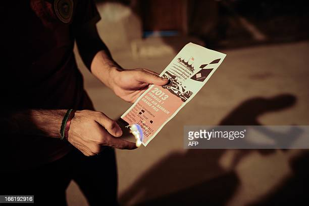 A Bahraini protestor sets on fire a leaflet for the upcoming Formula One Grand Prix which will take in Manama on April 21 during a rally in...