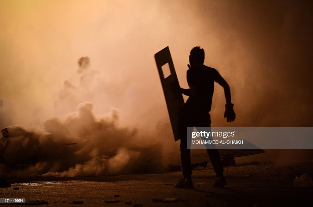 A Bahraini protestor stands amidst tear gas fired by riot police during clashes following a protest against the ruling regime in the village of Diraz, west of Manama, late on July 25, 2013. Bahrain has been shaken by protests by the Shiite majority against the regime of the Sunni Al-Khalifa dynasty since February 2011.