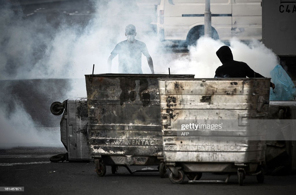 A Bahraini protestor take cover from tear gas fired by plainclothes police during clashes following an anti-government rally against the national dialogue talks on February 11, 2013, in the village of Sanabis, west of the Bahraini capital Manama. Bahrain's key political players launched a new round of talks to try to resolve the kingdom's two-year crisis, after opposition groups made a last-minute decision to join a national dialogue.