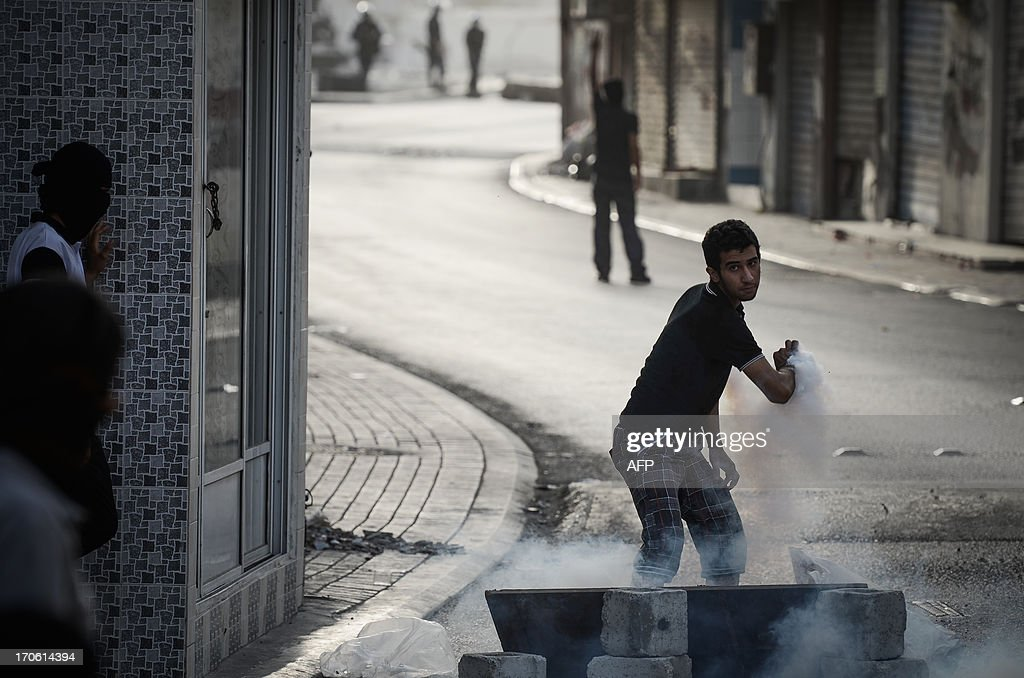 Bahraini protestor try to throw away a tear gas canister fired by riot police during clashes following a protest to demand more rights and against the ruling regime in the village of Bilad al-Qadeem, in a suburb of Manama, on June 15, 2013. Weekly protests, that began in 2011, are held by Bahraini Shiite Muslims demanding more rights from the ruling Sunni Muslim dynasty.