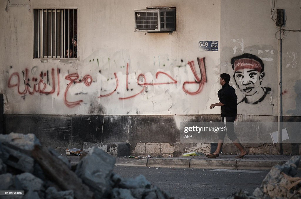 A Bahraini protestor walks next to a wall covered in graffiti that reads in Arabic, 'No dialogue with the killers' during clashes with riot police following an anti-government rally to demand political reforms on February 13, 2013 in the village of Sitra, South of the Bahraini capital Manama. Thousands of Bahraini Shiites took to the streets on the eve of the second anniversary of their crushed uprising, as a national dialogue aimed at ending a political stalemate resumed. AFP PHOTO/MOHAMMED AL-SHAIKH