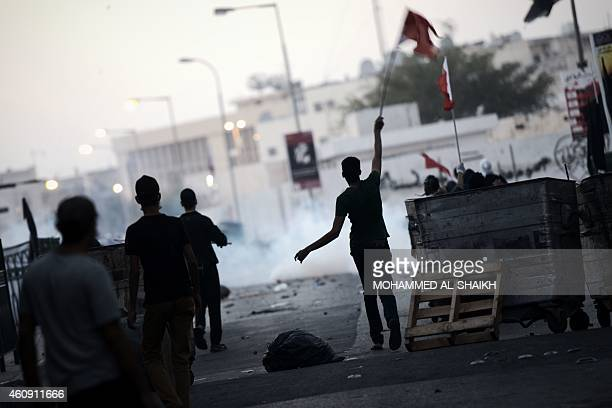 A Bahraini protestor waves his national flag during clashes with riot police following a demonstration against the arrest of the head of the banned...