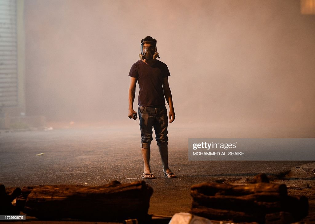 A Bahraini protestor wearing a gas mask stands amidst tear gas fired by riot police during clashes following a protest to demand more rights and against the ruling regime in the village of Diraz, West of Manama, in the early hours of July 19, 2013. Earlier in the week the interior ministry banned a planned opposition rally set for after Friday prayers following a car bombing outside a Sunni mosque in a neighbourhood where the royal court is situated.