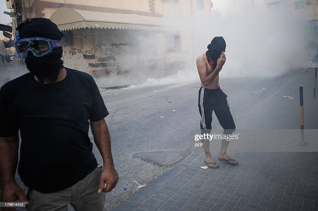 Bahraini protestors protect themselves from tear gas fired by riot police during clashes following a protest to demand more rights and against the ruling regime in the village of Bilad al-Qadeem, in a suburb of Manama, on June 15, 2013. Weekly protests, that began in 2011, are held by Bahraini Shiite Muslims demanding more rights from the ruling Sunni Muslim dynasty. AFP PHOTO/MOHAMMED AL-SHAIKH