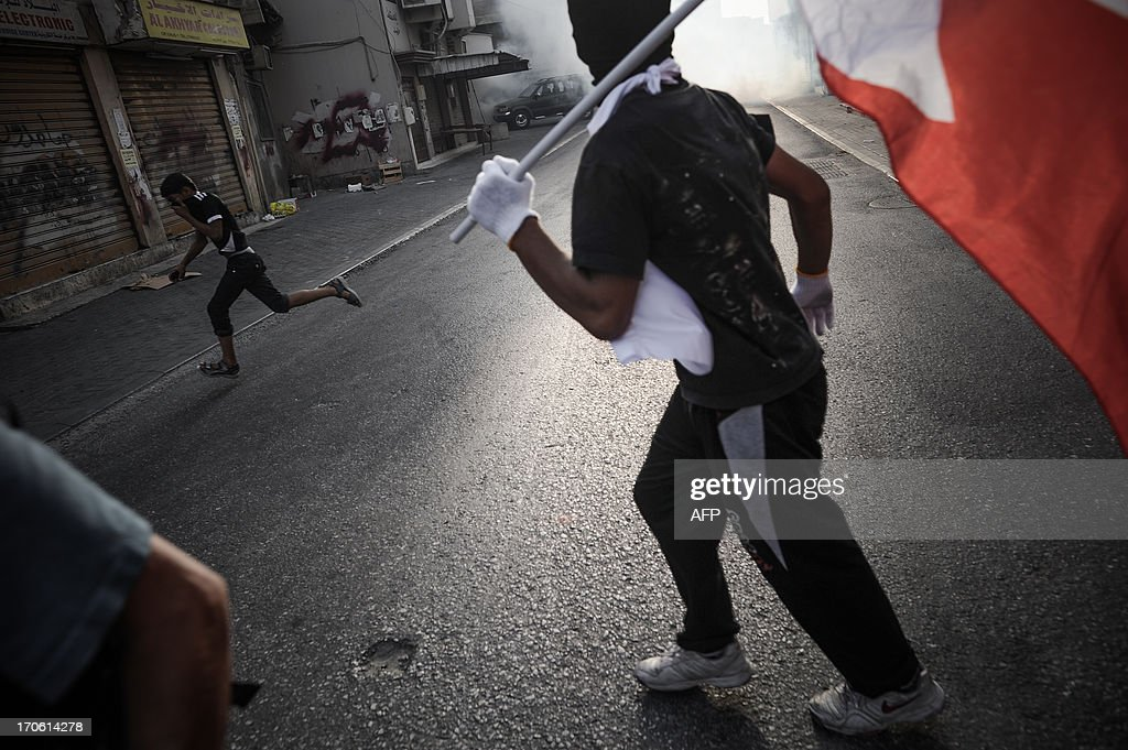 Bahraini protestors run for cover from tear gas and bird shots fired by riot police during clashes following an a protest to demand more rights in the village of Bilad al-Qadeem, in a suburb of Manama, on June 15, 2013. Weekly protests, that began in 2011, are held by Bahraini Shiite Muslims demanding more rights from the ruling Sunni Muslim dynasty. AFP PHOTO/MOHAMMED AL-SHAIKH