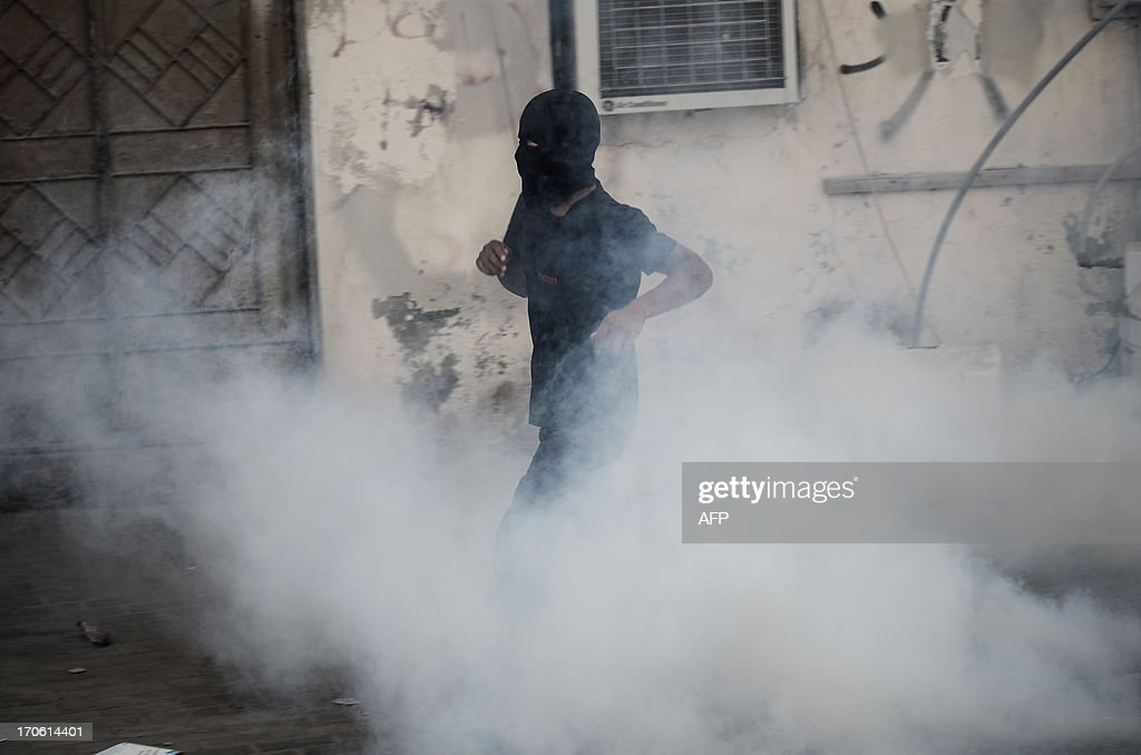 Bahraini protestors run for cover from tear gas and bird shots fired by riot police during clashes following an a protest to demand more rights and against the ruling regime in the village of Bilad al-Qadeem, in a suburb of Manama, on June 15, 2013. Weekly protests, that began in 2011, are held by Bahraini Shiite Muslims demanding more rights from the ruling Sunni Muslim dynasty.