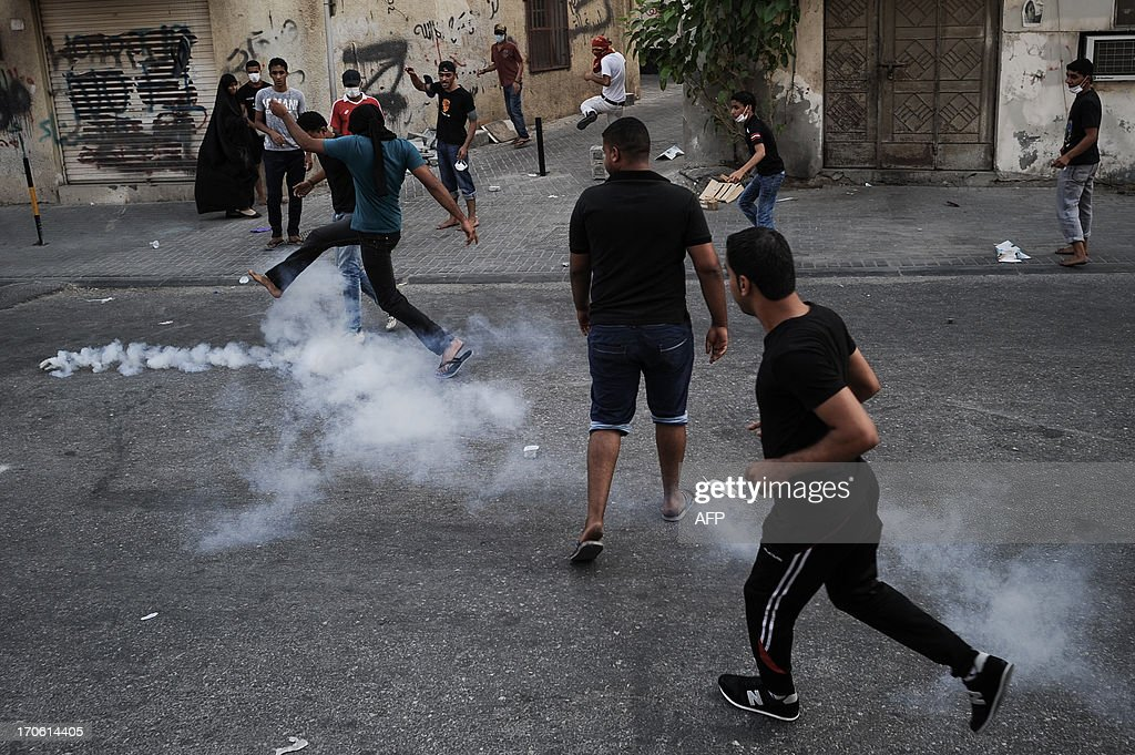 Bahraini protestors run for cover from tear gas and bird shots fired by riot police during clashes following a protest to demand more rights and against the ruling regime in the village of Bilad al-Qadeem, in a suburb of Manama, on June 15, 2013. Weekly protests, that began in 2011, are held by Bahraini Shiite Muslims demanding more rights from the ruling Sunni Muslim dynasty.