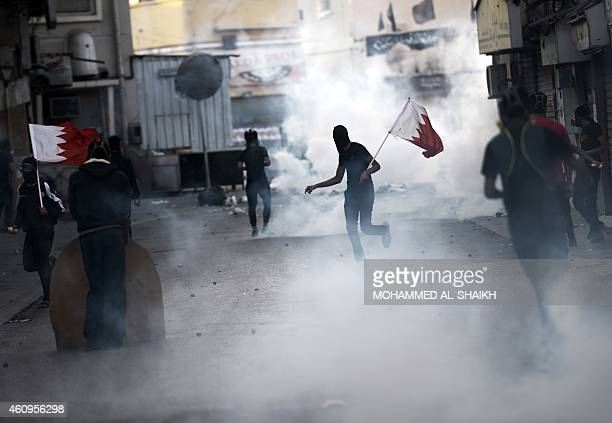 Bahraini protestors run for cover from tear gas during clashes with riot police following a protest against the arrest of the head of the banned...