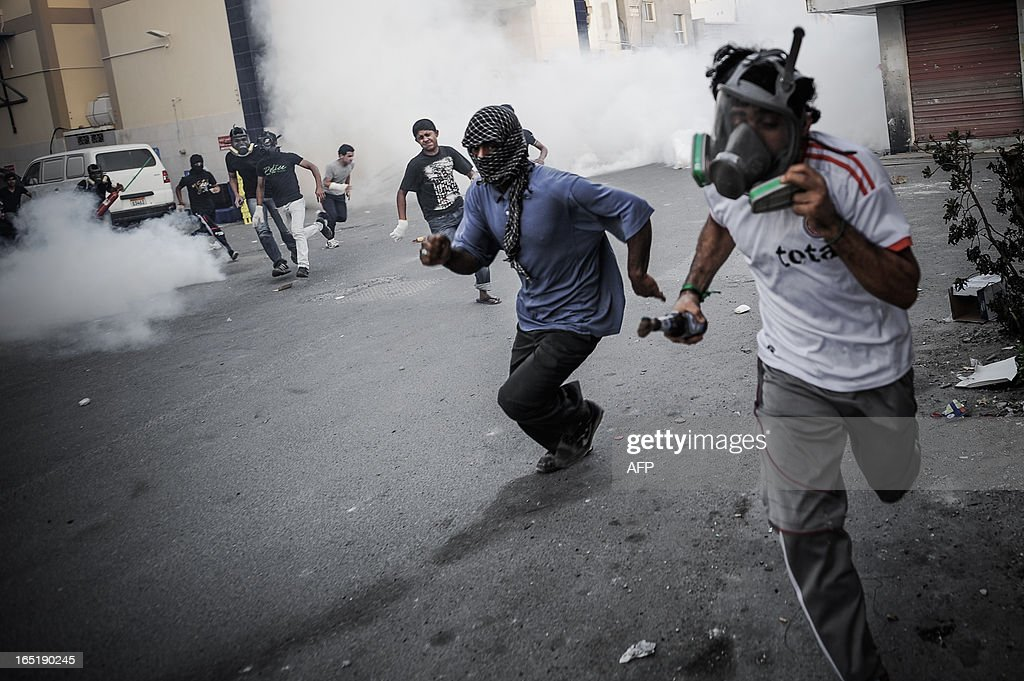 Bahraini protestors run for cover from tear gas fired by riot police during clashes following the funeral of Abd Al-Ghani Al-Rayes in the village of Diraz, west of Manama on April 1, 2013 Al-Rayes, who was 66-years old, died in front of a police station following what medics presume was a heart-attack, as he was trying to find out what happened to his arrested son, family said. AFP PHOTO/MOHAMMED AL-SHAIKH