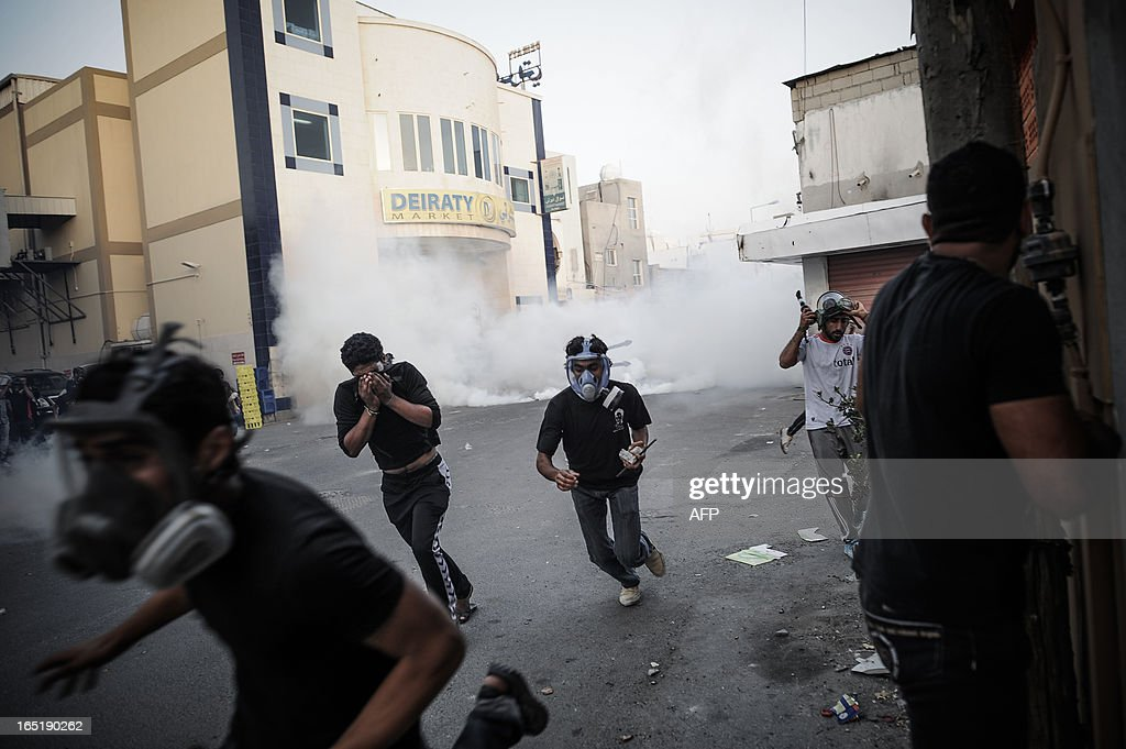 Bahraini protestors run for cover from tear gas fired by riot police during clashes following the funeral of Abd Al-Ghani Al-Rayes in the village of Diraz, west of Manama on April 1, 2013 Al-Rayes, who was 66-years old, died in front of a police station following what medics presume was a heart-attack, as he was trying to find out what happened to his arrested son, family said.