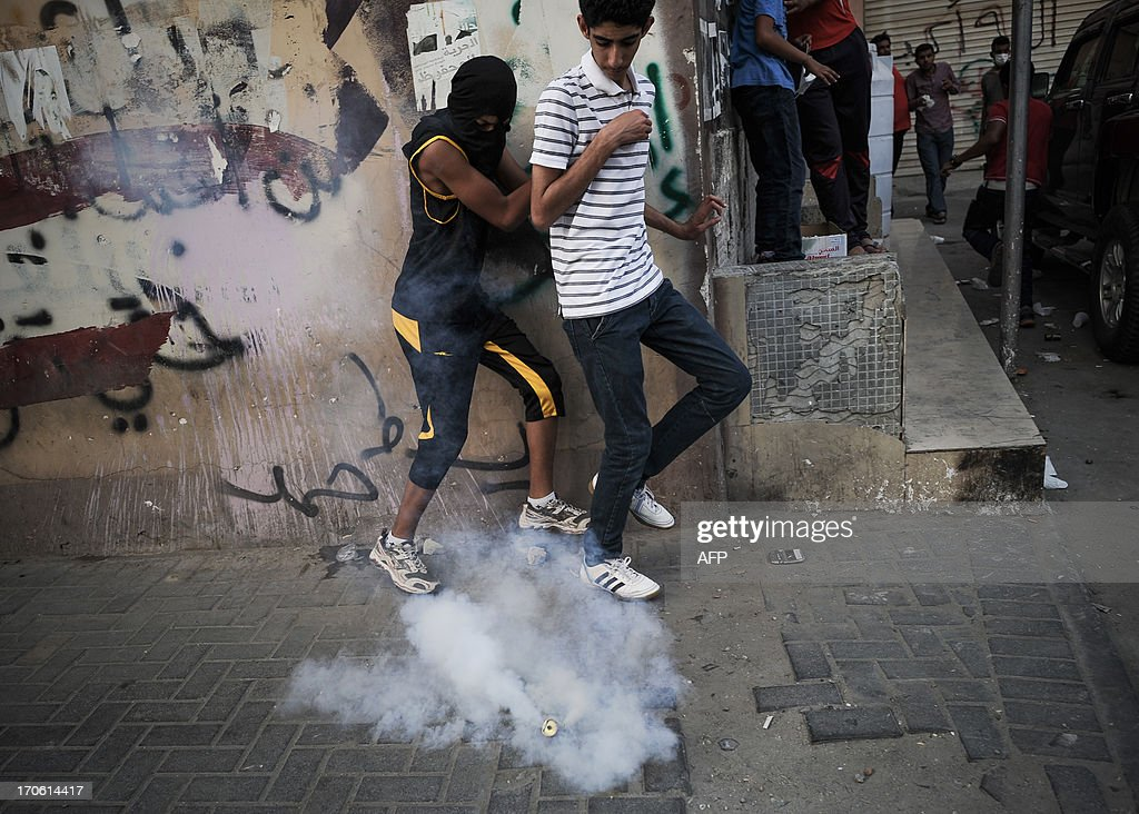 Bahraini protestors run for cover from tear gas fired by riot police during clashes following a protest to demand more rights and against the ruling regime in the village of Bilad al-Qadeem, in a suburb of Manama, on June 15, 2013. Weekly protests, that began in 2011, are held by Bahraini Shiite Muslims demanding more rights from the ruling Sunni Muslim dynasty.