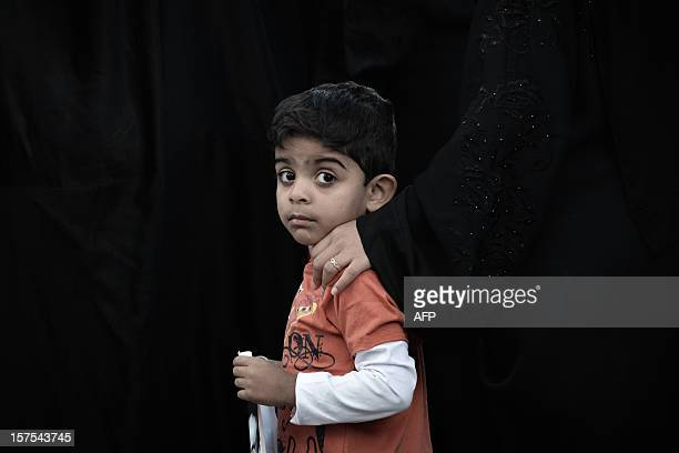 A Bahraini Shiite Muslim boy takes part to a demonstration in solidarity with political prisoners and against the government in the village of...