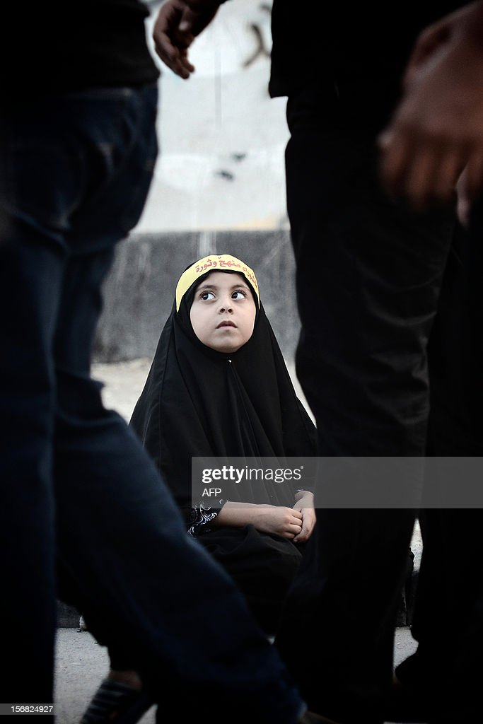 A Bahraini Shiite Muslim girl with a banner on her head participates in a ceremony marking Ashura, which commemorates the seventh century slaying of Imam Hussein, the grandson of Prophet Mohammed, in the village of Sanabis, west of Manama, on November 22, 2012. The Gulf state has experienced unrest since March last year when the authorities crushed protests led by the Shiite Muslim majority demanding greater rights. Arabic writing on banner reads 'Ashura is an approach and revolution'.