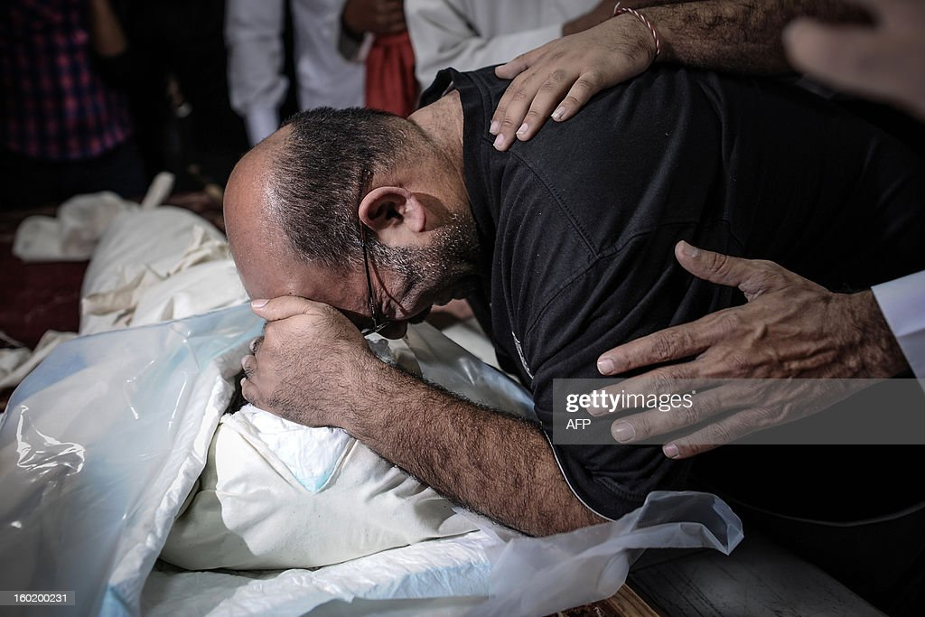 A Bahraini Shiite Muslim man mourns in front of the corpse of his eight-year-old son, during his funeral on January 27, 2013 in the village of Daih, west of Manama. The child, Qassim Habib Marzooq, died at hospital after developing respiratory complications and his relatives claim that his death is due to the inhalation of poisonous tear gas that riot police used during a protest in January 2013.