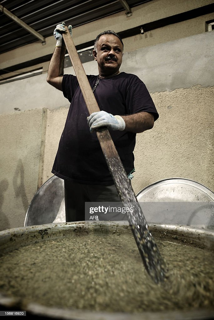 A Bahraini Shiite Muslim man prepares food for the participants in the ceremony marking Ashura, which commemorates the killing of Imam Hussein by armies of the caliph Yazid in 680 AD, in the village of Sanabis, west of Manama, late on November 21, 2012.